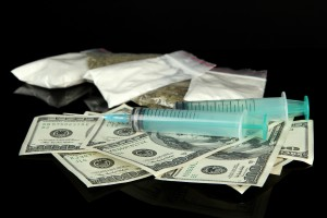 Drugs, money and  syringes, isolated on black